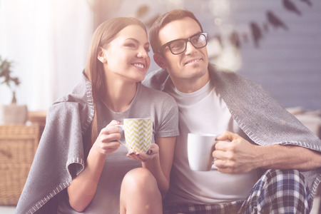 Portrait of positive couple while drinking tea