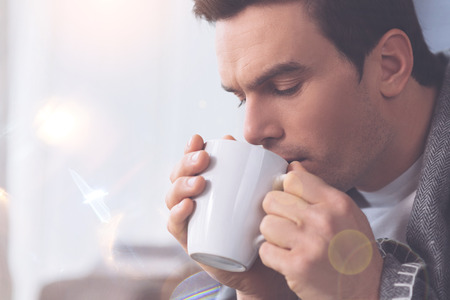 Portrait of sick male person keeping cup near lips
