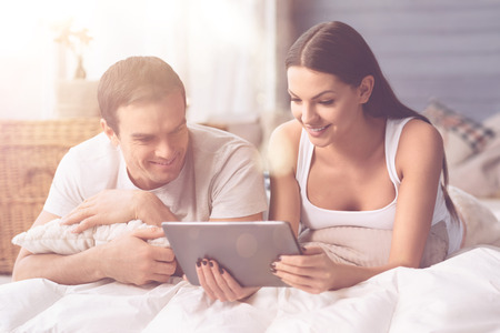 Delighted couple watching something on the tablet