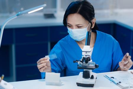 Intelligent smart biologist studying microscope slides Stock Photo