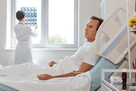 Depressed unhappy man lying on the hospital bed Stock Photo
