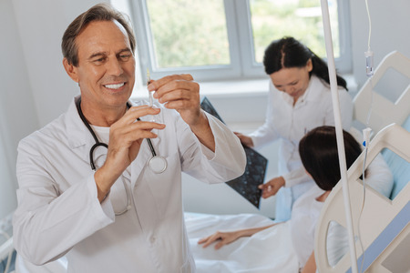 Happy joyful doctor preparing for an injection Stock Photo