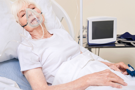 gerontology: Unconscious unstable lady wearing equipment for sustainable breathing Stock Photo