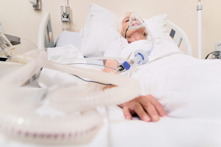 Ailing unstable woman breathing through special mask