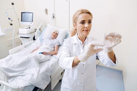 Scrupulous capable doctor carefully holding a syringe