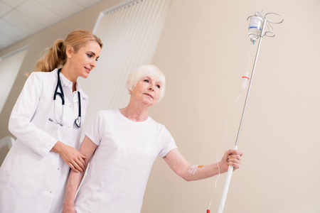Kind trained doctor assisting her elderly patient