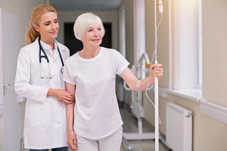 Optimistic bright doctor taking her patient for a walk