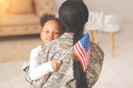 Little girl hugging her mother and holding a flag Stock Photo