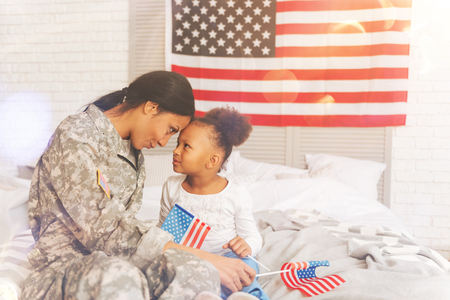 Military mother and daughter sitting forehead-to-forehead