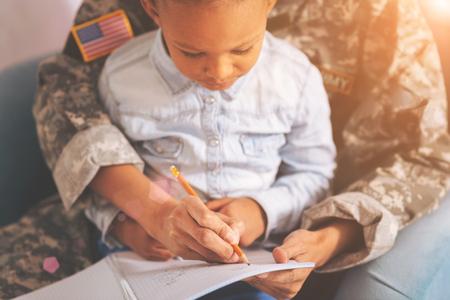 Militaire moeder met een kind op schoot maken van aantekeningen Stockfoto