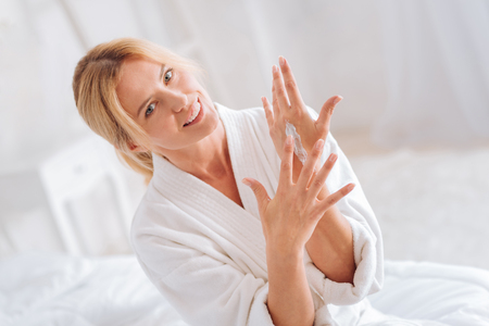 Portrait of delighted blonde that spreading cream on hand