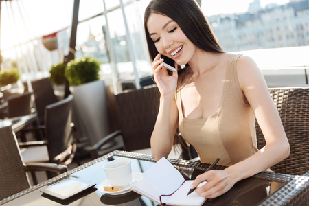 Delighted intelligent woman noting down information Stock Photo