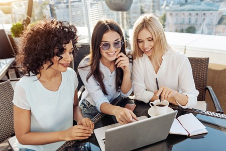 Happy positive woman pointing at the laptop screen Stock Photo