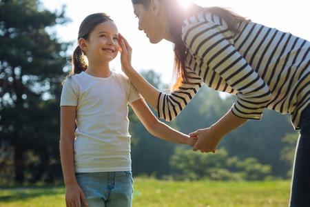 Gentle mother stroking her daughters cheek
