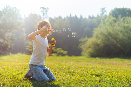 Little girl blowing bubbles while standing on her knees Stock Photo