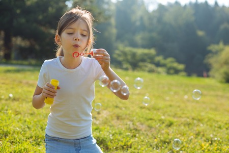upbringing: Cute little girl blowing soap bubbles in the forest