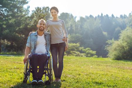 Femme et son mari avec handicap posant dans la prairie Banque d'images - 84156293