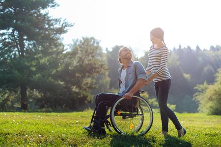 그녀의 장애인 남편의 휠체어를 들고 웃는 아내