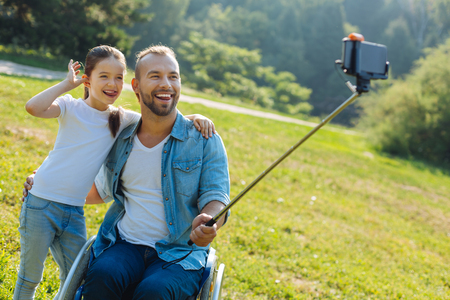 Father in a wheelchair and daughter posing for a selfie