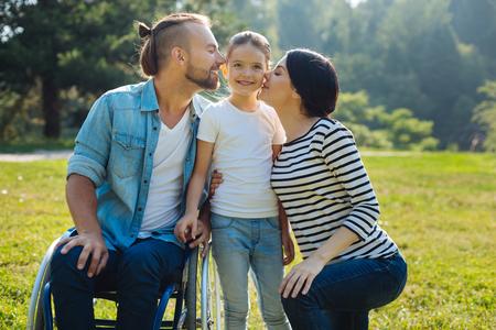 Mooie moeder en vader die hun dochter op wangen kussen
