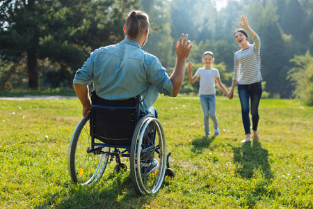 Young man with disabilities waving hello to his family Stock Photo