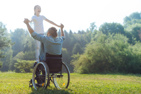 Niña de pie en el regazo de su padre en silla de ruedas