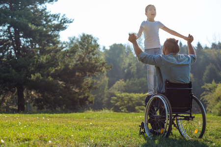 Mobility-impaired father holding his daughter on lap Stock Photo