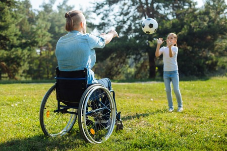 Man with disabilities playing volleyball with daughter
