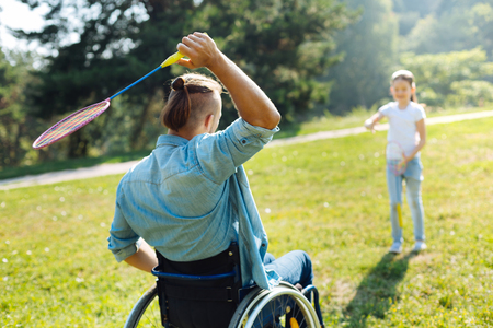 Mobility-impaired man passing shuttlecock to daughter Stock Photo