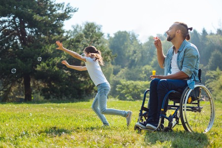 Cheerful disabled father and daughter playing with soap bubbles