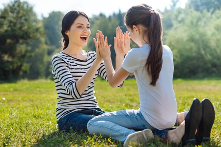 Happy mother and daughter playing pat-a-cake in park