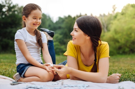 Girl taking a missing puzzle piece from mothers hands Stock Photo