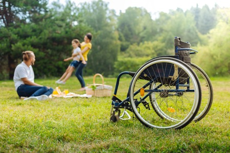 Disabled man watching his wife spin daughter Stock Photo