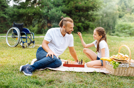upbringing: Smiling girl asking her father about chess figures Stock Photo