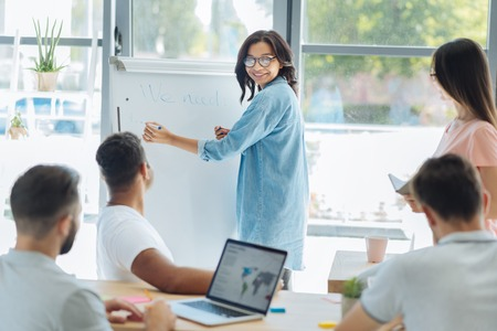 Positive delighted woman writing on the whiteboard Stock Photo