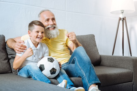 Grandfather and grandson rooting for their favorite football team