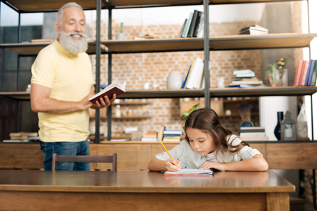 Joyful grandfather dictating words to his granddaughter