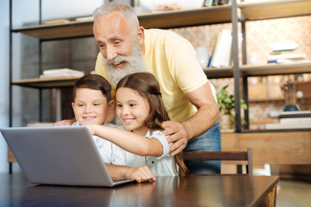 Adorable siblings and their grandfather making a group video call Stock Photo