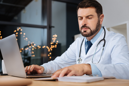 Serious experienced doctor reading his notes