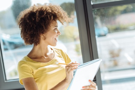 Cheerful afro american woman making notes