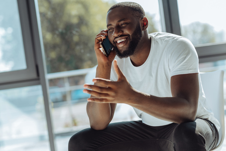 Overjoyed young afro american man talking on smartphone