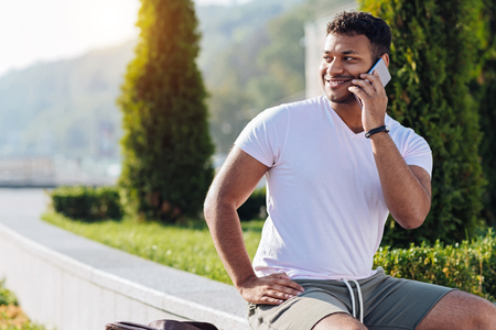 Positive delighted foreign man using telephone