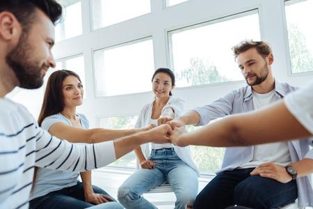 Gelukkige jonge mensen die een teambuilding activiteit doen