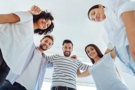 Joyful positive team standing together