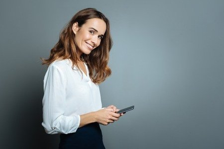 Positive delighted woman using her smartphone Stock Photo