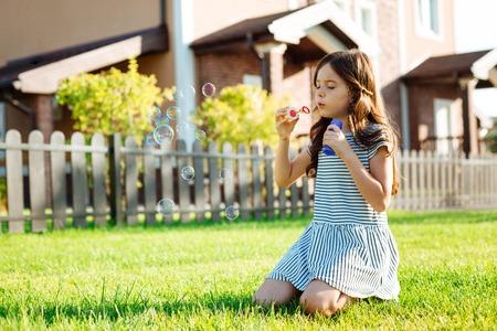 Cute little girl blowing soap bubbles Stock Photo