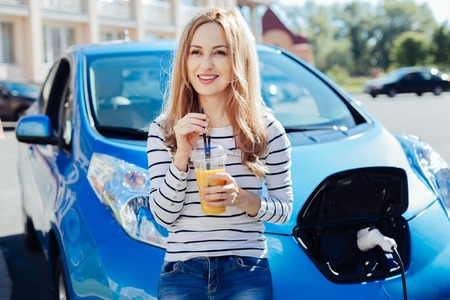 Delighted happy woman leaning on the car bonnet