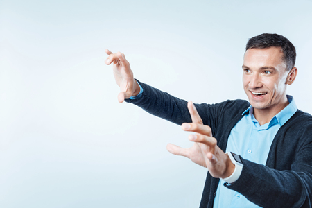 Excited mature gentleman using invisible screen