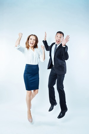 Emotional colleagues getting excited together over background Stock Photo