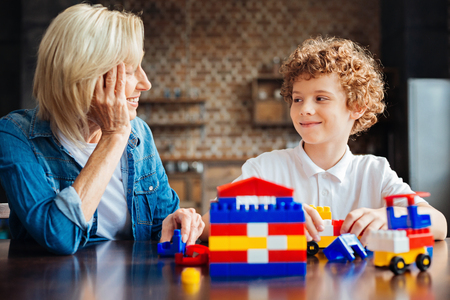 Smart curly haired kid spending time with grandmother